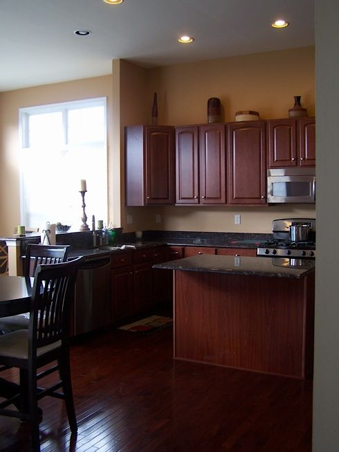 cherry cabinets with dark flooring and a dark countertop ...