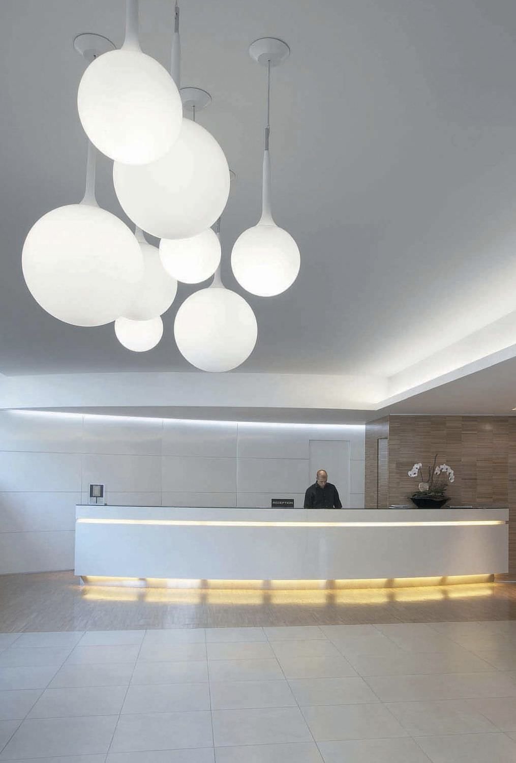 A Grouping Of Ca Pendant Lamps By Artemide Provide Diffused Lighting While Making Striking Sculptural Statement