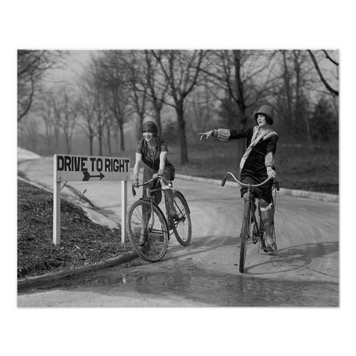Flapper girls taking a bicycle ride in the park. Circa 1925.
