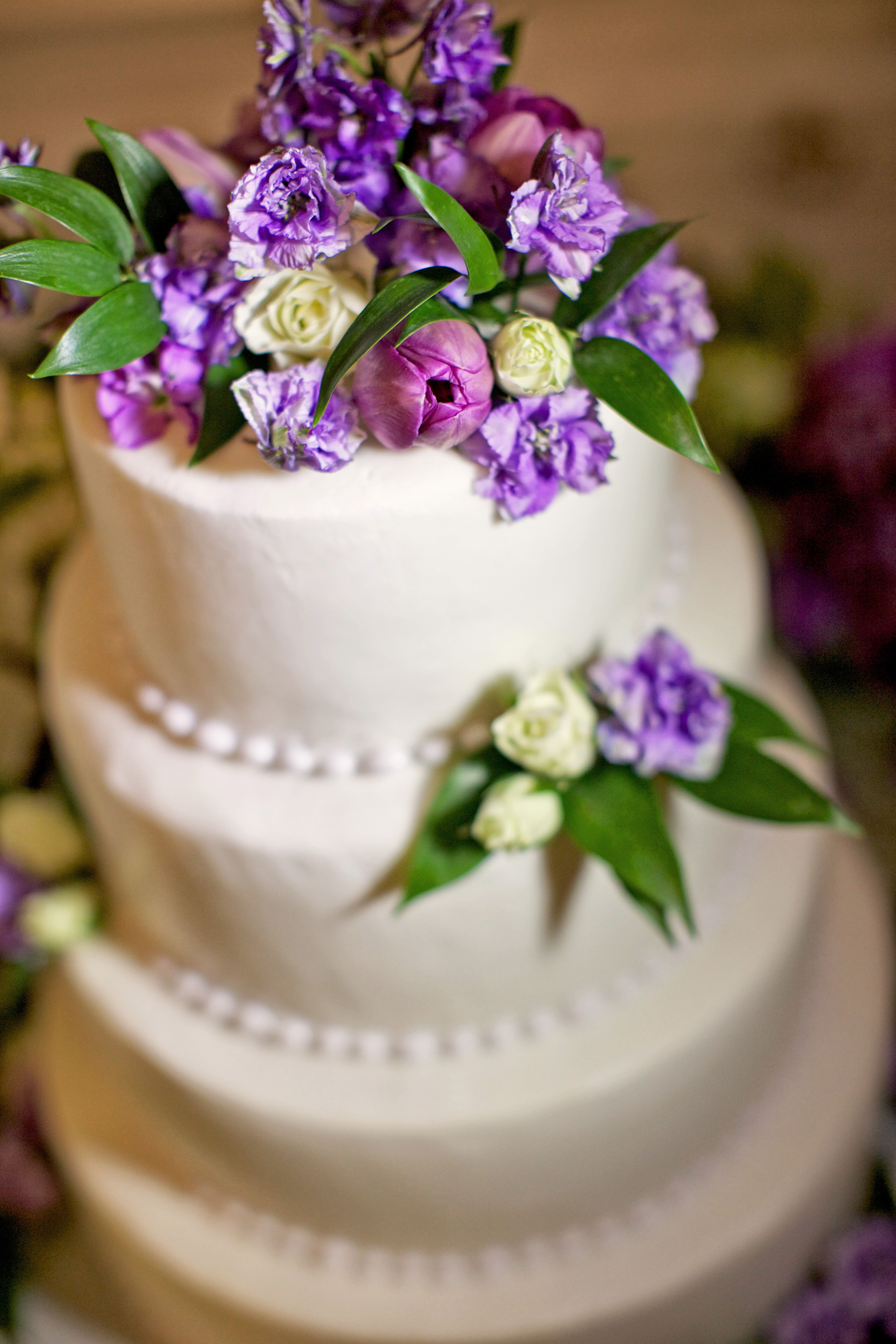 A wedding cake accented with purple flowers at the Inn at