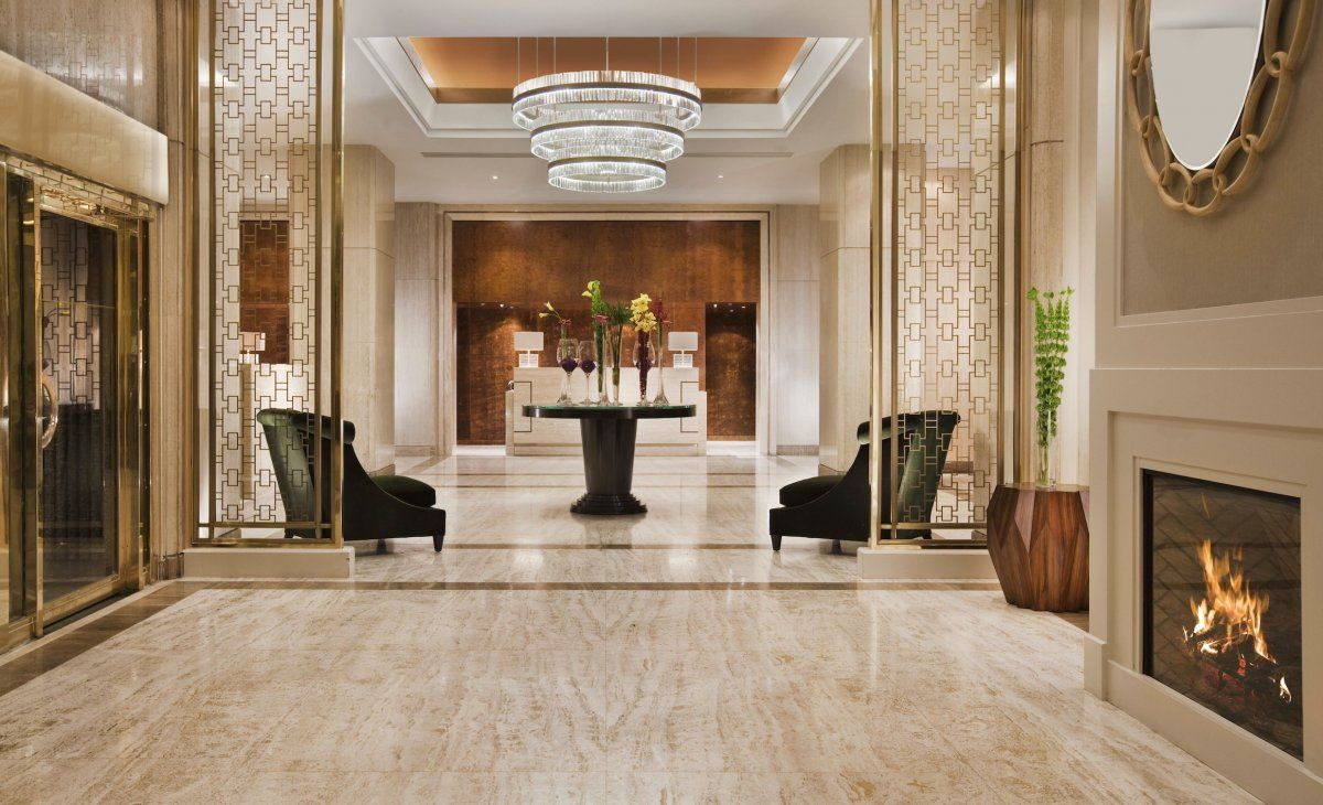 Luxury lobby residence interior decor hall with modern fireplace under round mirror design ideas and glamorous interior with marble tile and