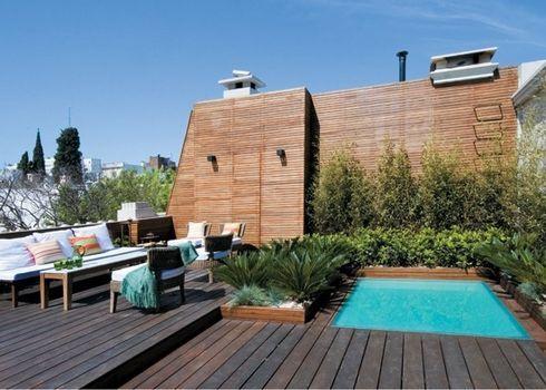 piscina en terraza con deck de madera y paisajismo