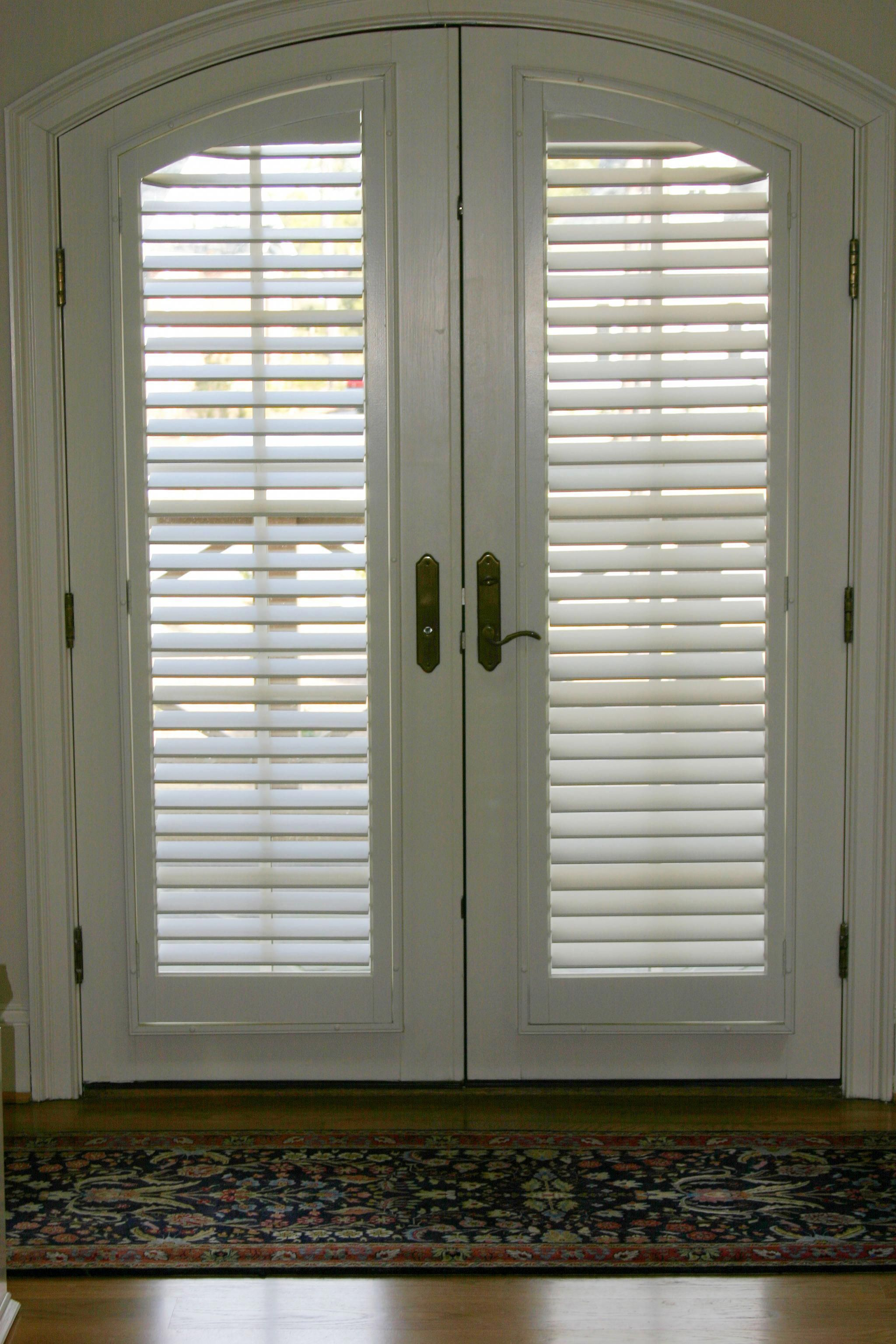 Beautiful french doors with arched windows covered with our custom plantation shutters plantation shutters look great from the inside and outside views