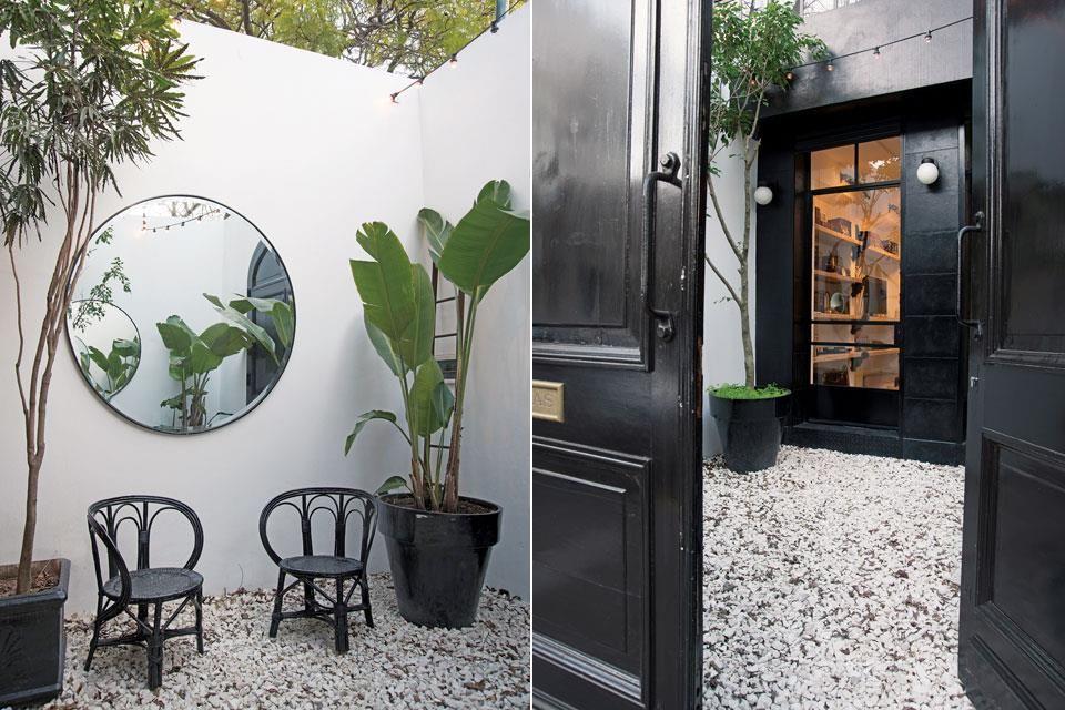La puerta doble de demolición marca el acceso principal y tras ella aparece el jardín seco con piedra partida, sillas 'Mar del Plata' pintadas y macetas negras con grandes strelitzias.  Foto:Living /Pompi Gutnisky