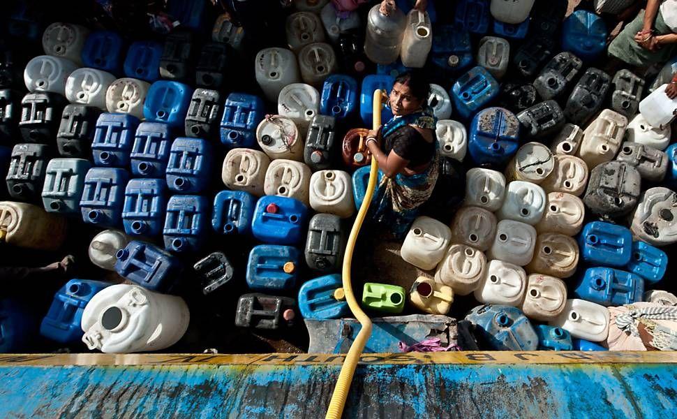 Mulher indiana enche potes com àgua em Nova Déli; diversas partes da cidade estão com o abastecimento racionado, na Índia