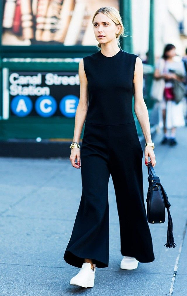 b04f09afbb Mix up your outfit by styling a black jumpsuit with start white shoes.