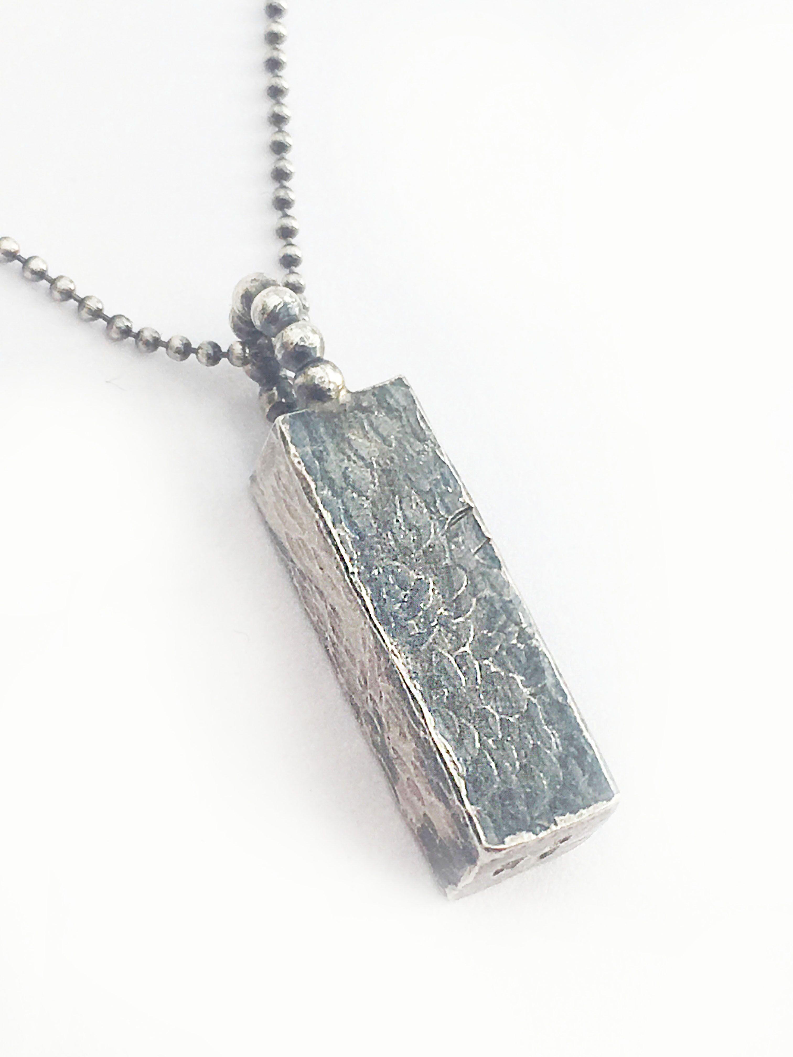 A chunky handmade silver pendant mirrors the rocks