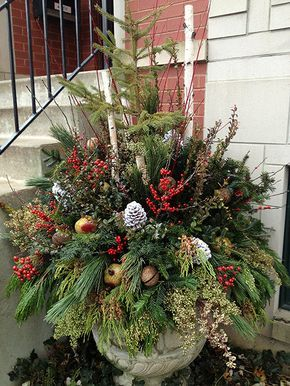 christmas urn with very full mixed greenery pine cones ornaments berries twigs