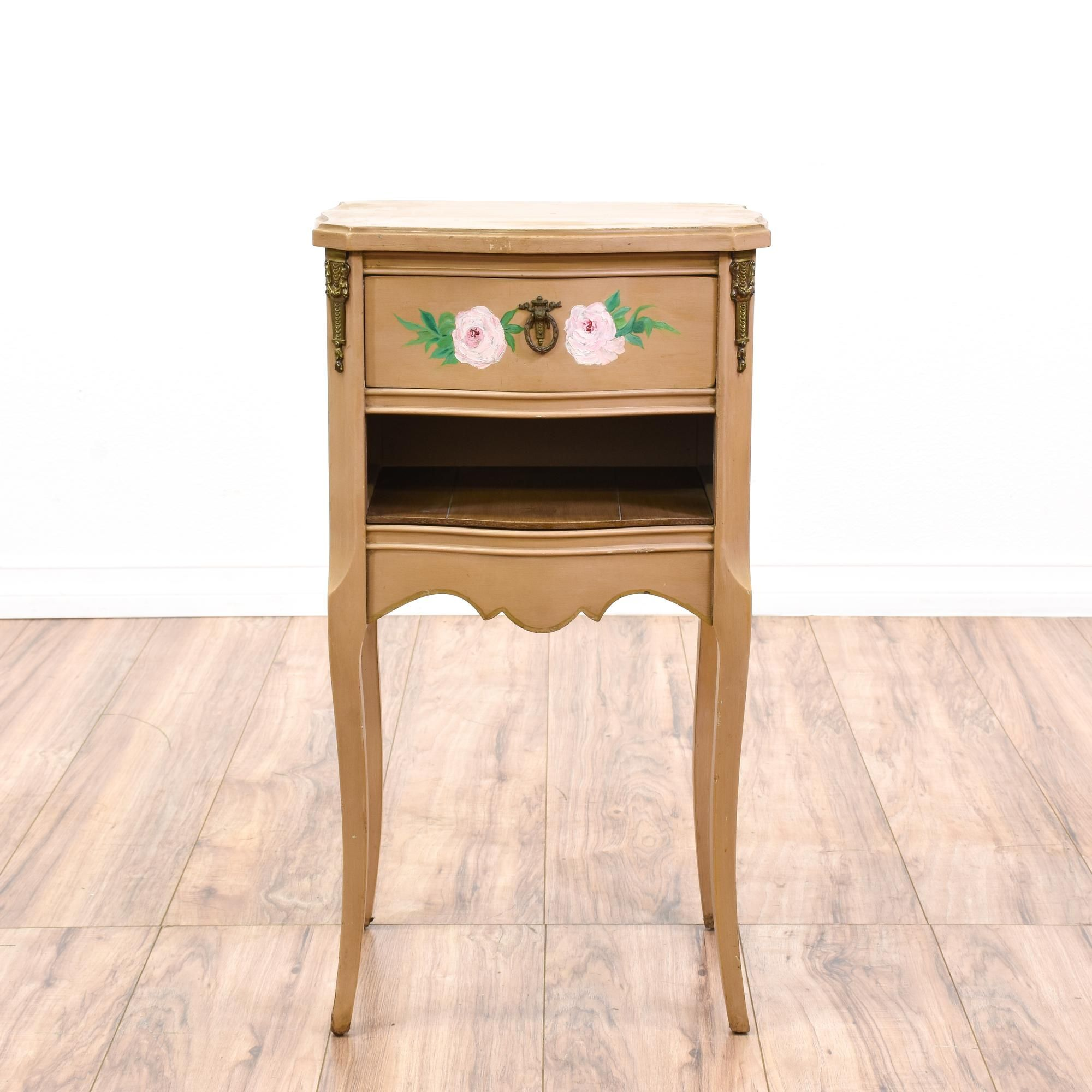 This cottage chic nightstand is featured in a solid wood with a fresh tan paint finish and hand painted floral details. This end table has delicate curved legs, 1 drawer and a bottom cubby cabinet. Adorable bed side table with the perfect amount of storage! #cottagechic #dressers #nightstand #sandiegovintage #vintagefurniture