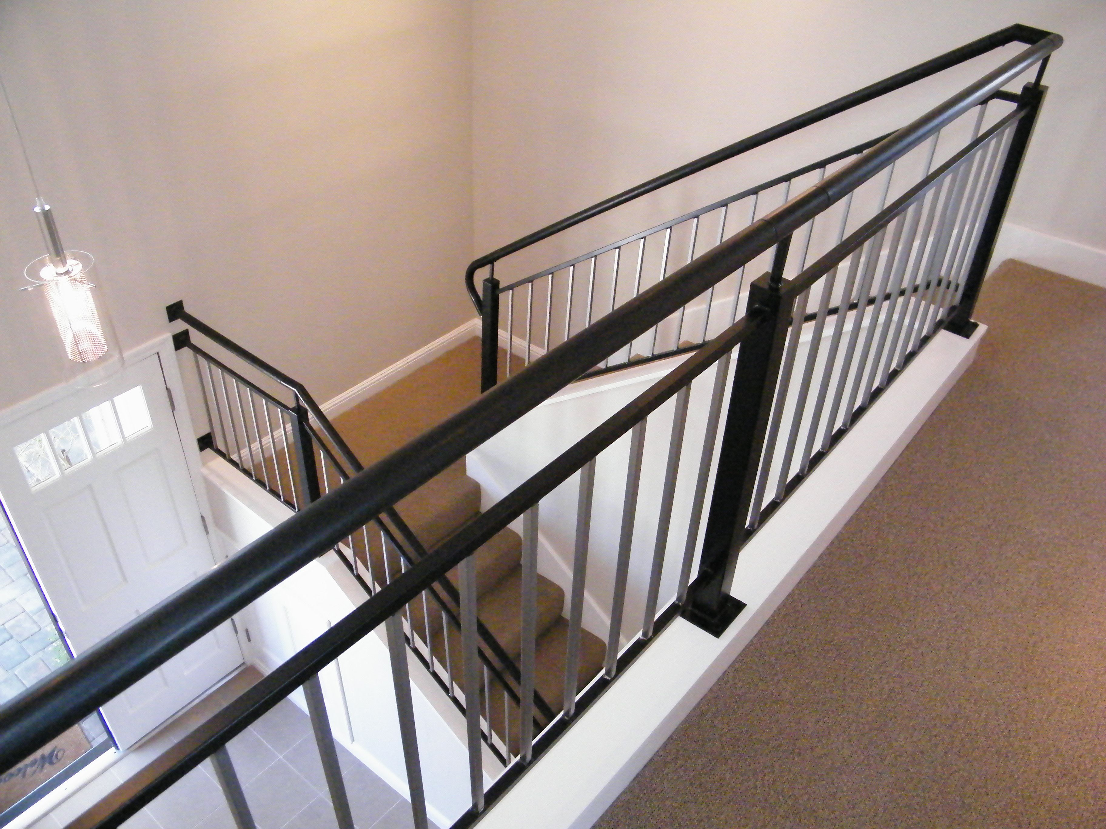Wood and iron railing, curb mounted on stair riser allows for an open airy entry to the the second story hall.