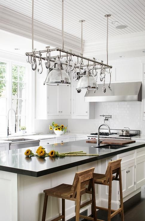 A cook's kitchen features a beadboard tray ceiling accented with a stainless steel pot rack hanging over a white center island topped with Absolute Black Granite fitted with a prep sink and a gooseneck faucet lined with a freestanding stained baking island on wheels topped with white marble.