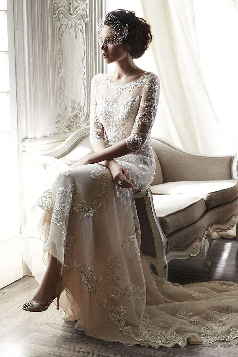 A dramatic illusion lace back and illusion sleeves adorn this hand-embellished sheath #gown, glimmering with metallic lace appliqués and