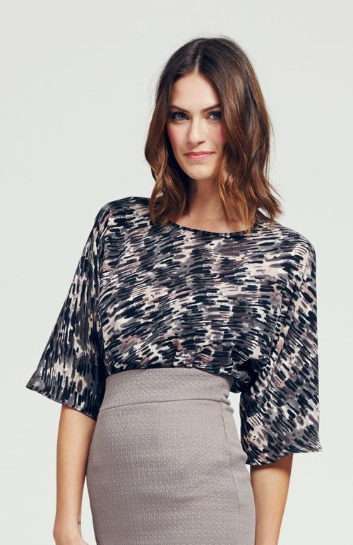 Loose and flowy fitted top. Mid length sleeves. Slight bateau neckline. Subtle side slit detail at waist. Dry Clean Only.