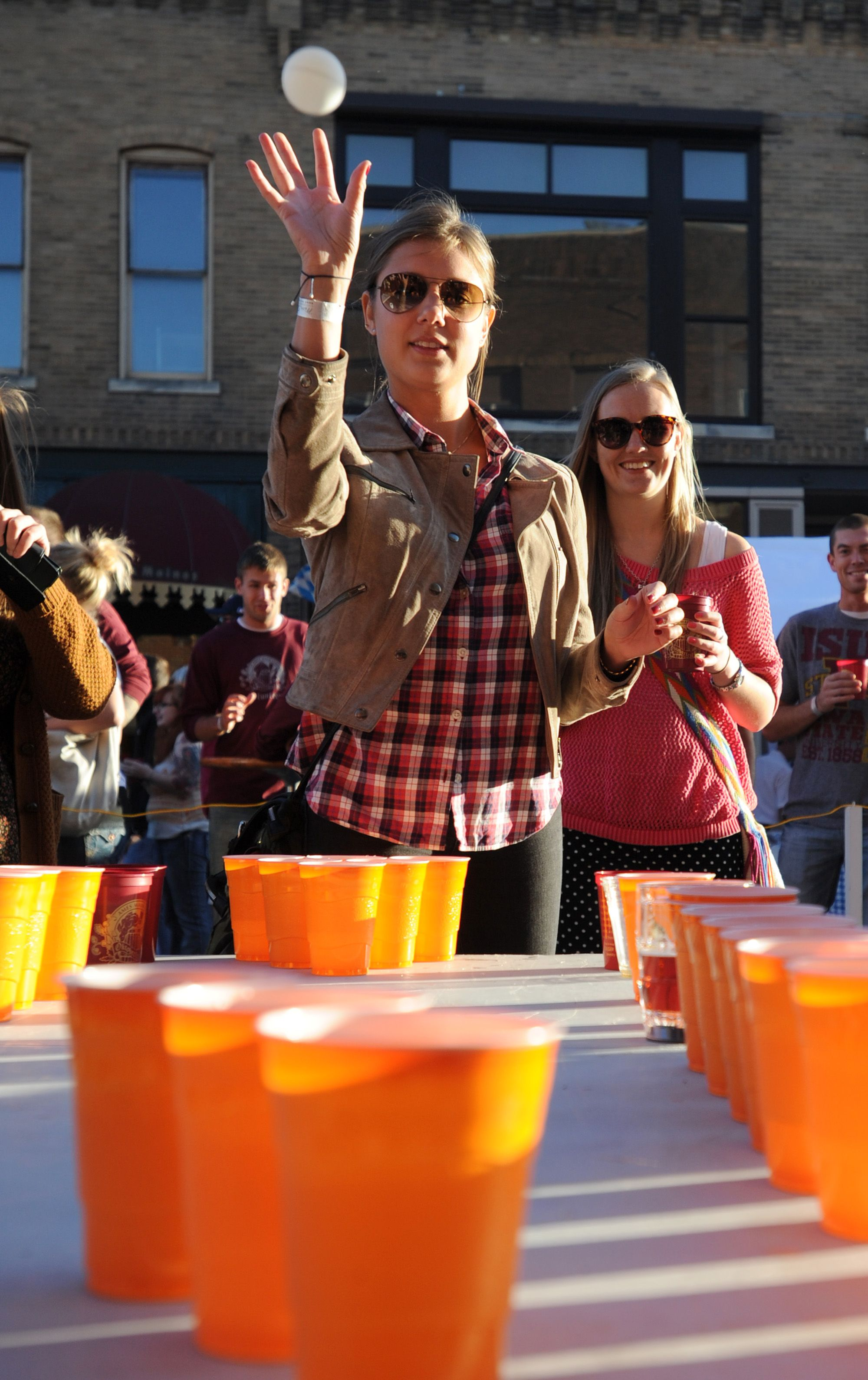 Lina Rylander throws a ping pong ball into a cup during a