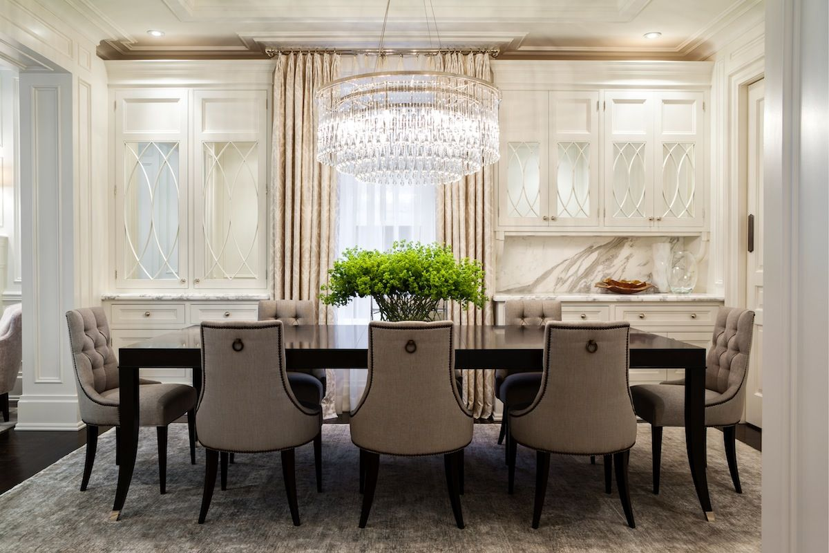 Traditional Dining Room With Art Deco Chandelier Illuminating Black  Lacquered Dining Table Surrounded By Gray Tufted Dining Chairs