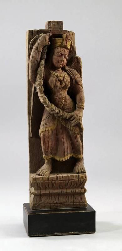 An Indian wooden carving of a winged woman holding a garland, 19th century, possibly an architectural fragment, carved wearing a turban with long flowing hair, her gaze to the right, wearing long flowing robes, mounted on a later stand, 42.5cm. high - Price Estimate: £200 - £400