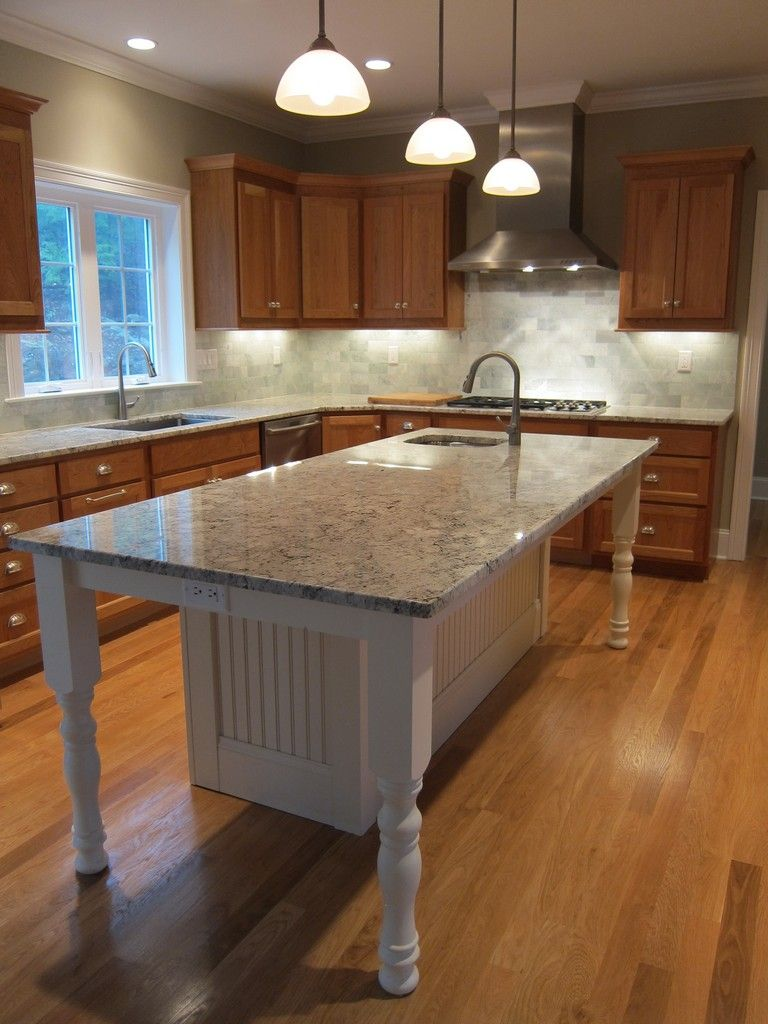 white kitchen island with granite countertop and prep sink. island