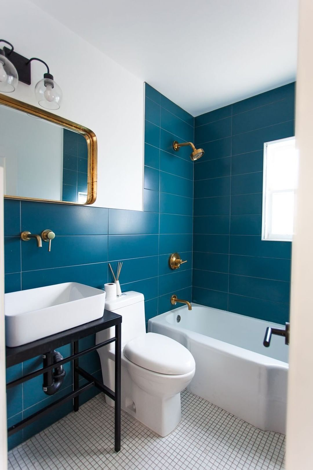 While This Bathroom S Courageous Focal Point Is The Blue Tile The Designer Brightened Up The Space With A Bathroom Trends Blue Bathroom Tile Bathroom Interior