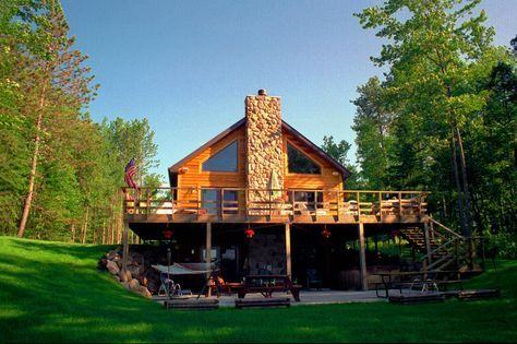 Chalet style home on a walk out basement with cedar siding and a stone chimney in the middle