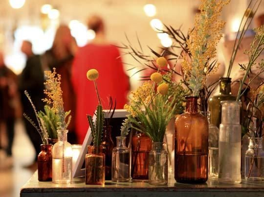 Vintage medicine bottles as vases sets off the flowers with a warm, old-timey feel.