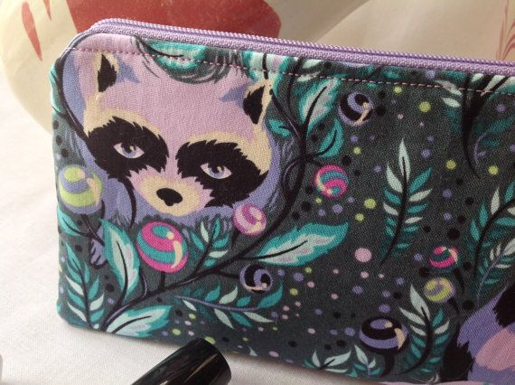 This cute and functional zipper case/pouch is made of a 100% cotton print with a teal background and the sweetest racoon faces with bushy, bushy, bushy striped tails. The case is fully lined with a cream swirl fabric. Beautiful double lines of decorative embroidery.  The shape of the case is sleek with curved corners at the top towards the zipper for a secure side-to-side closing. The bottom edges are rounded for a lovely finish. This case is flat overall.