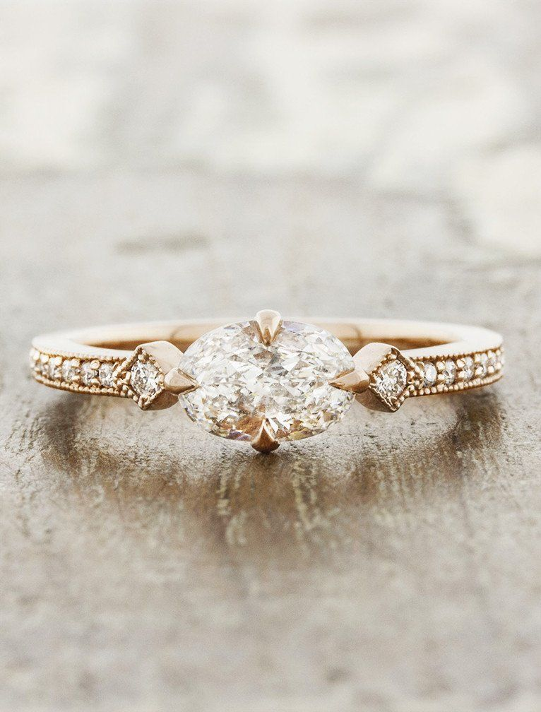 The Charleen is an art deco inspired engagement ring - with an oval diamond in a horizontal position, nestled between 0.18tcw of brilliant round white diamonds in a rose gold band.