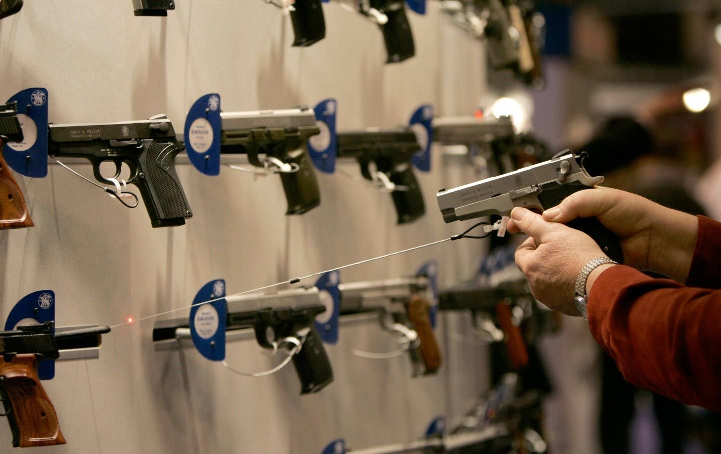 A woman points a handgun with a laser sight on a wall display of other guns during the National Rifle Association convention in St. Louis.