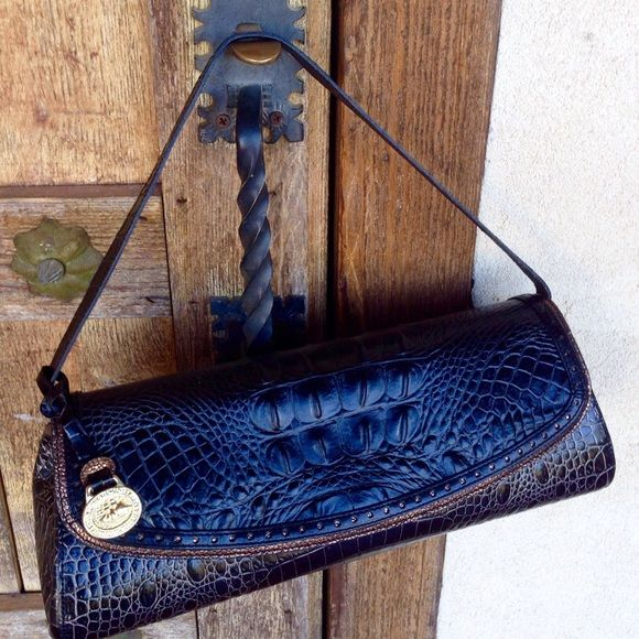"""Leather Black & Bronze Brahmin Faux Croc Bag NWT She's my favorite Brahmin bag of all time! Why sell her? I carry too much stuff & this ole Cowgirl just can't learn new trix! Stunning Authentic Black Leather with Faux Croc Texture you can't beat! Bronze Leather trim around magnetic flap & Bronze underside of Flap. She's 13"""" long & 4"""" Wide at the bottom, 11.5"""" Long at the top. Inside is Taupe Faux Suede fabric with Bronze leather Key Fob, Zip Pocket & 2 slip Pockets. Full length pocket on…"""