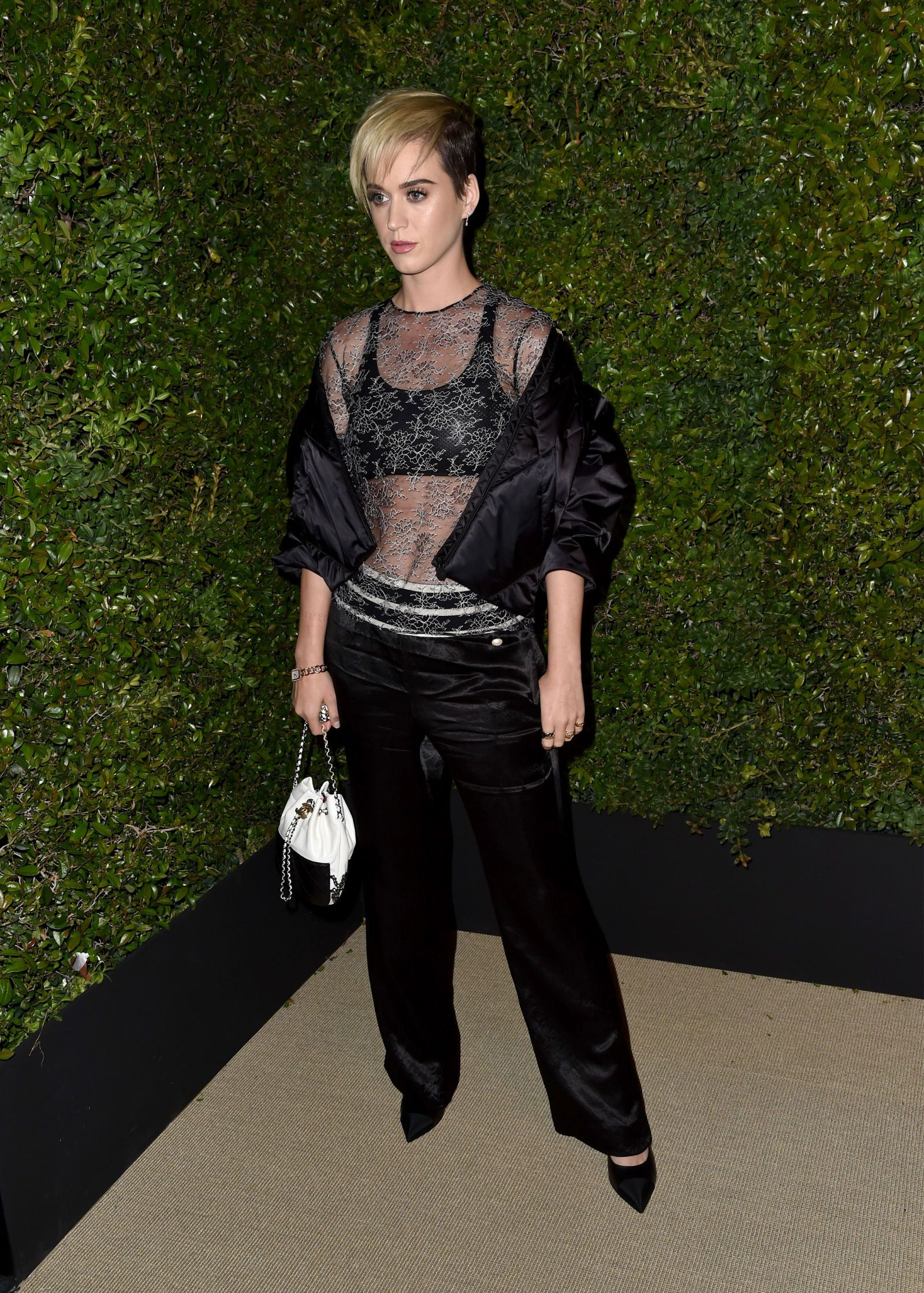 Katy Perry rocked a chic sports bra, sheet shirt and her cropped cut at the Chanel dinner party.
