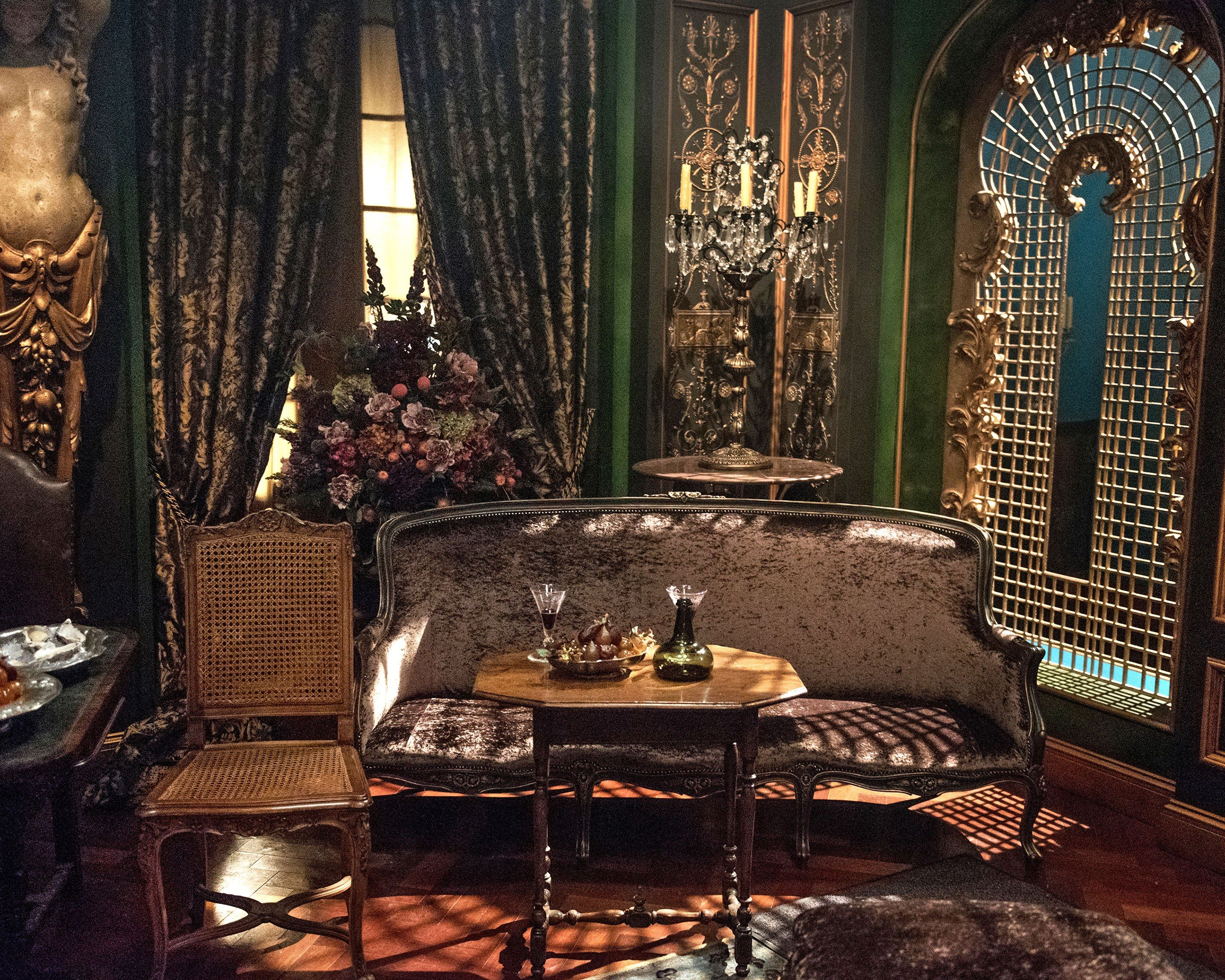 """Steele went for broke with teal velvet walls and shimmering moldings in the brothel set. The pièce de résistance is what Steele refers to as """"the carved ladies,"""" one of which is shown here."""