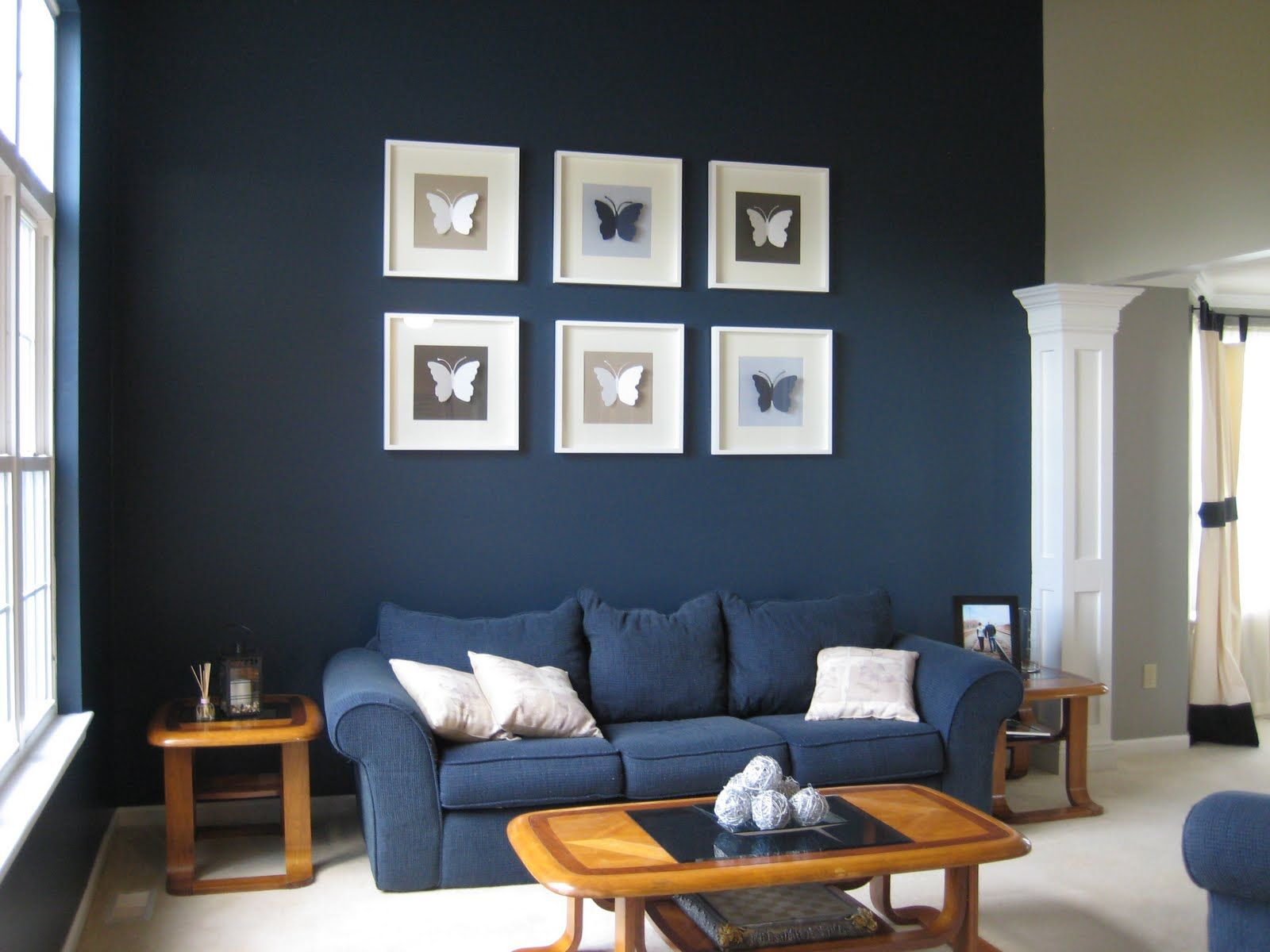 Pretty White Picture Frame With Wooden Material On Dark Blue Painted Wall Together Black Butterfly Image And Also Fabric Sofa Cushi