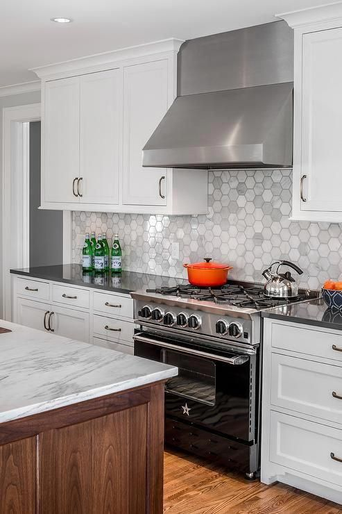 A stainless steel hood mounted against large hexagon marble backsplash tiles is flanked by white shaker cabinets and positioned above a black BlueStar Range located between white cabinets accented with oil rubbed bronze pulls and a charcoal gray quartz countertop. #whiteshakercabinets