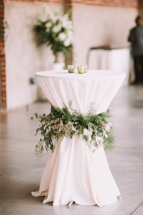 Photo of cocktail tables with a floral arrangement instead of a ribbon that your guests w…