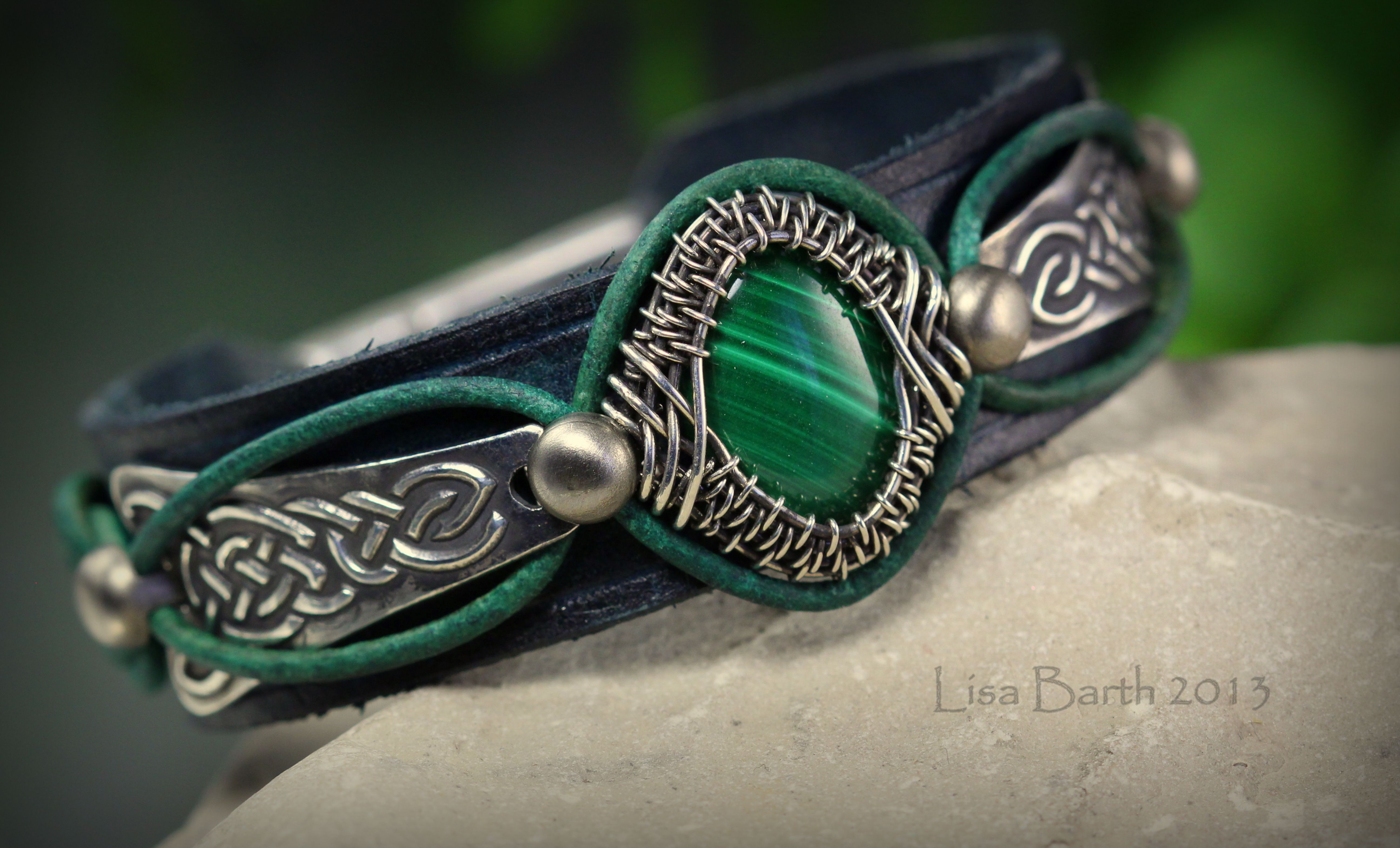 This one is a combination of hand dyed leather, metal clay side pieces and wire work to hold the malachite cab in place.  I am finding it interesting to mix mediums. --Lisa Barth