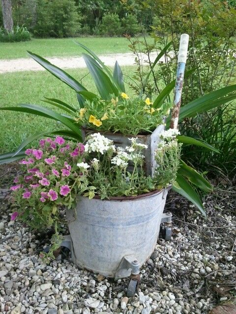 Yard art old rusty metal mop bucket turned into a planter for Metal bucket planter