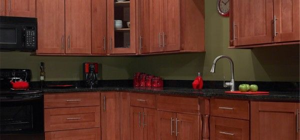 shaker kitchen cabinets in beautiful cherry wood with brushed silver pulls and black countertop only