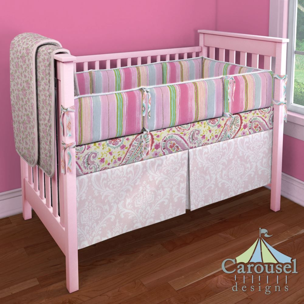 Crib bedding in Pink Osborne Damask, Pink Rosettes, Solid Pink, Primrose Stripe, Pastel Tribal, Watercolor Paisley. Created using the Nursery Designer® by Carousel Designs where you mix and match from hundreds of fabrics to create your own unique baby bedding. #carouseldesigns