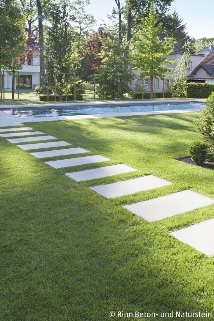 Schrittplatten im Gras verlegt: Der Trend des Jahres! Man langt gemütlich von Terrasse zum Pool, barfuß auch, zum Beispiel über das Gras in den Zwischenräumen. Eine tolle Weggestaltung, die maximalen Platz für die Natur lässt! #design #rinnbeton #gartengestaltung #kräutergartendesign