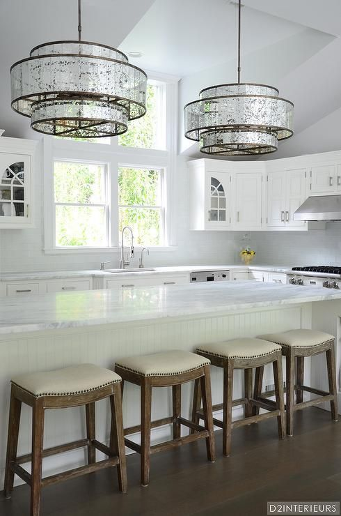 A pair of Currey  Co Fantine Chandeliers illuminate a long white beadboard kitchen island with turn A pair of Currey  Co Fantine Chandeliers illuminate a long white beadb...