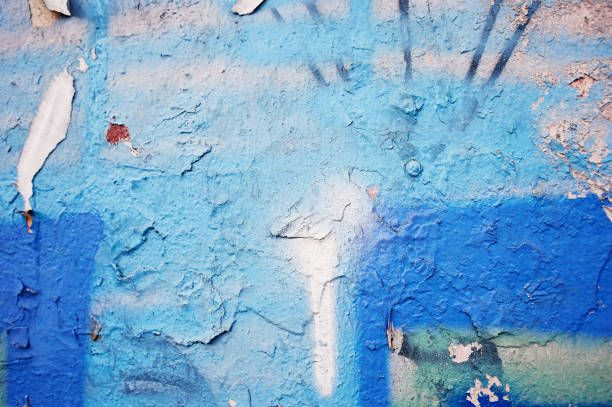 blue peeling paint on a concrete wall