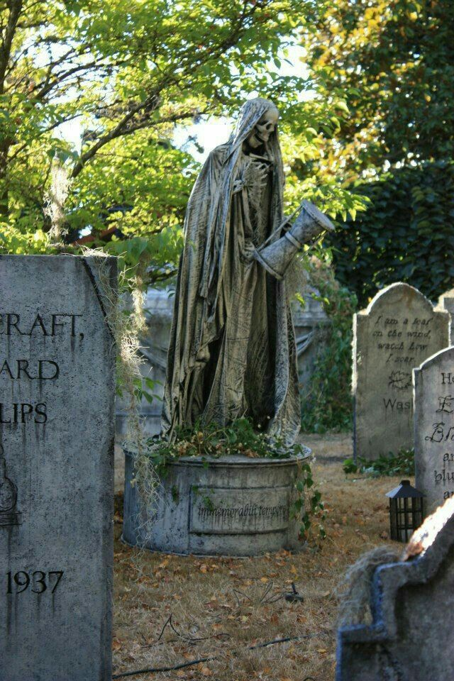 A very eerie statue if the Grim Reaper in a Cemetery ...