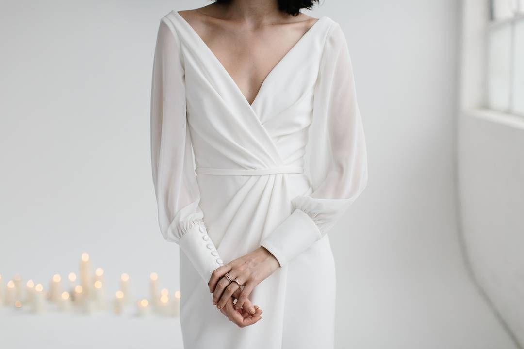 NICKI / We are excited to announce that our highly anticipated 'Nicki' gown will be in our Melbourne, Brisbane, Alexandria + New York stores by the weekend! This wide V-neckline wrap gown drapes elegantlyover the bust. Long, sheer georgette bell sleeves gather perfectly into a slim cuff. Back is open cut and low.Make an appointment now to try on this gown now! @kwhbridal 📷 - @kas.richards • mua @makeupbysophieknox • space - @xostudios • model - @peyton__edwards