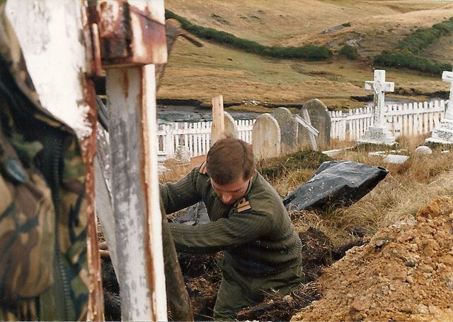 A Royal Marine digs a grave for a fallen comrade