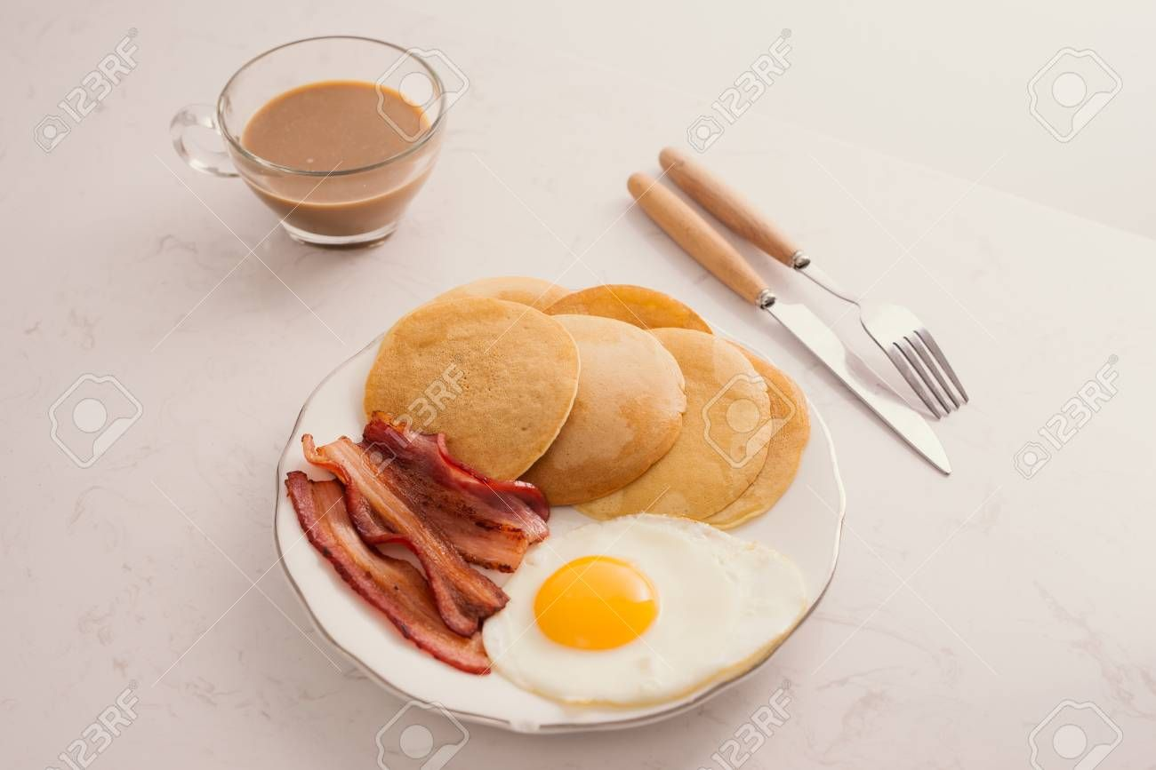 Breakfast plate with pancakes, eggs, bacon and fruit. ,