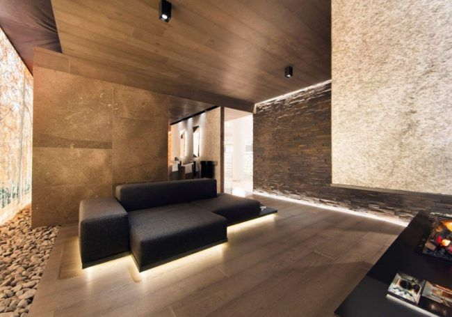 Indirekte Beleuchtung Wandgestaltung Wohnzimmer Couch Holzboden Naturstein