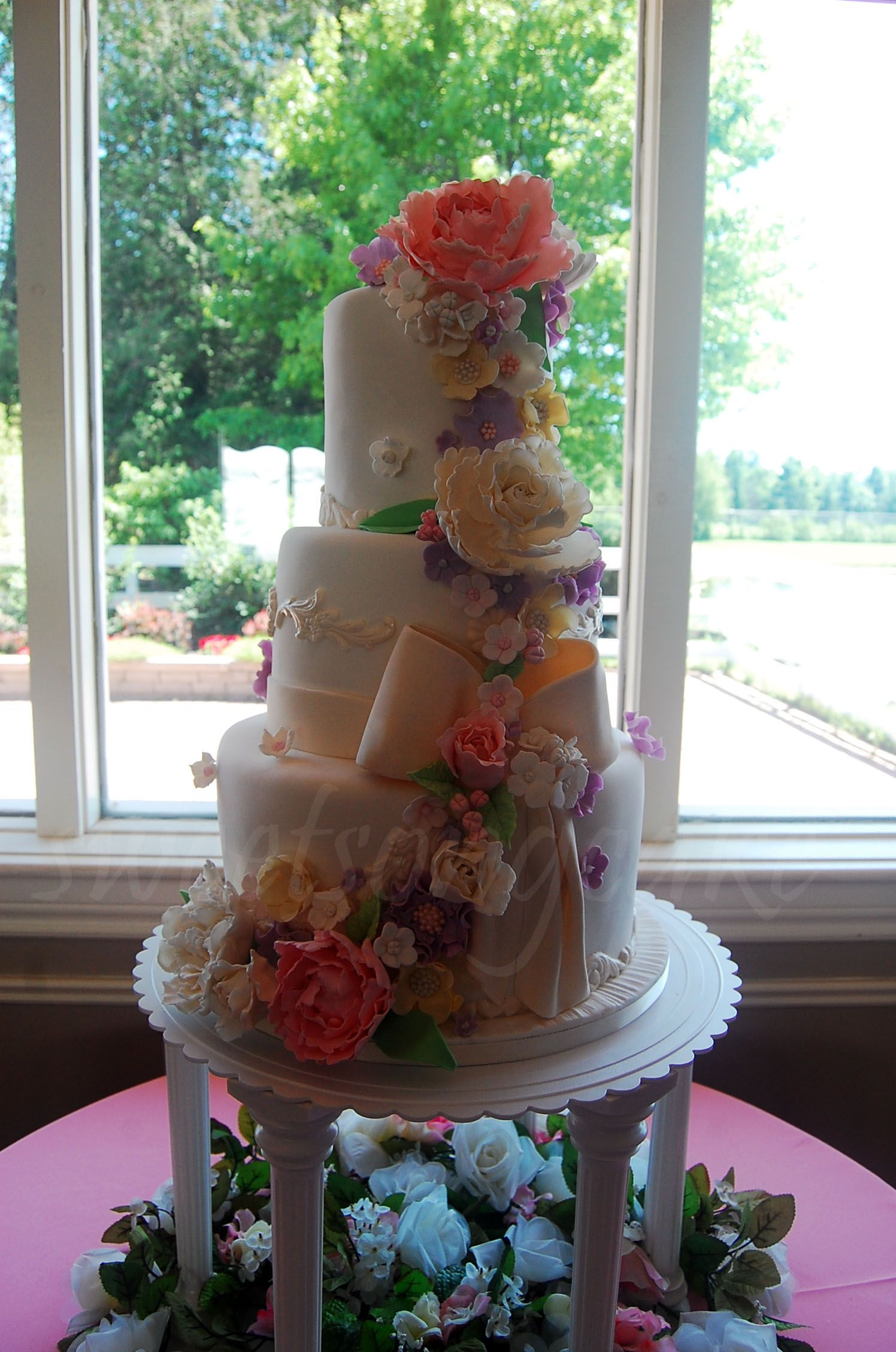 Spring blossom tiers wedding cake with cascade from flowers