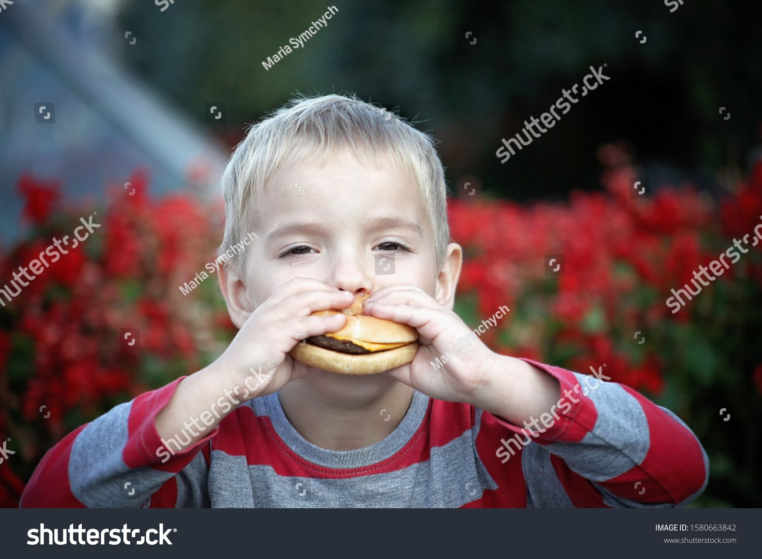 Funny Hungry Small Boy Eating A Burger At The Street In Summer Food And Drink Concept Healthy Childhood Outdoor Emotional Lifes Hungry Funny Small Boy Funny