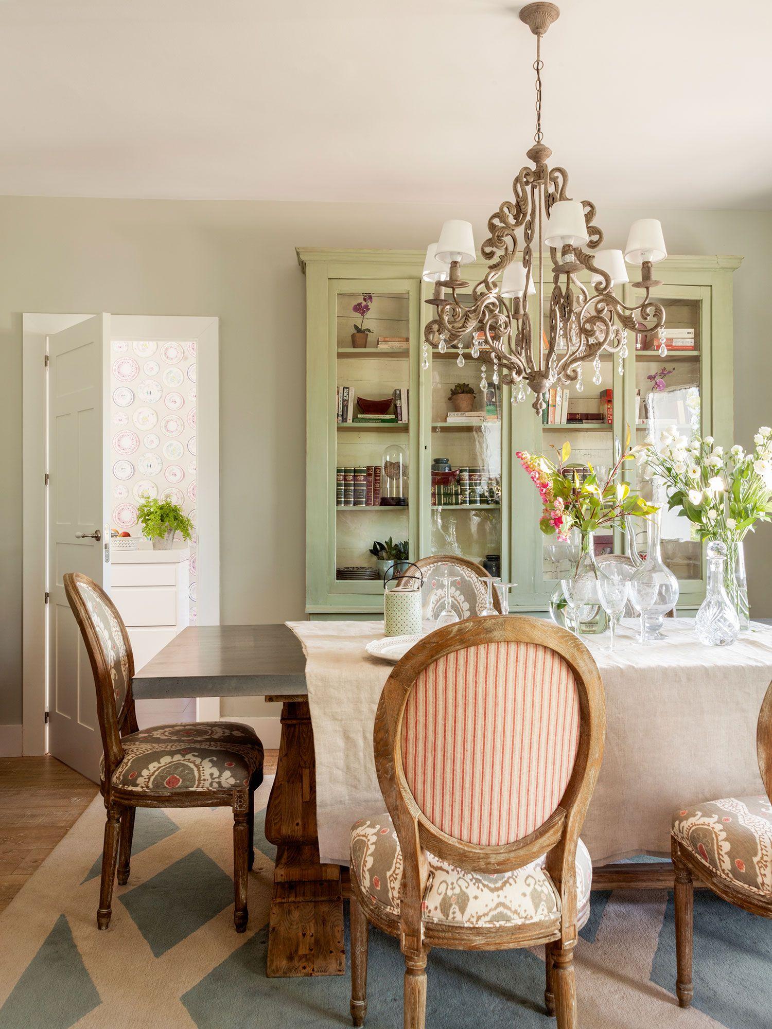 Comedor con sillas clásicas tapizadas con estampados y librería al fondo