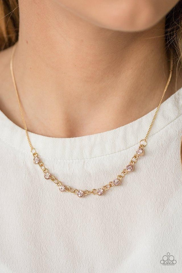 Encased in sleek gold frames, dainty pink rhinestones link below the  collar, creating delicate hints of sparkle. Features an adjustable clasp  closure.