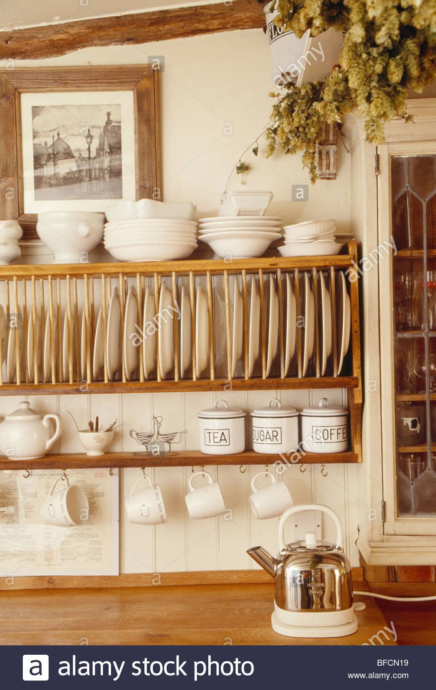 Stock Photo - Close-up of cream bowls and cups on wooden plate rack
